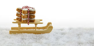 wooden sled in the snow with cinnamon stars, traditional christmas cookies, background with copy space fades to white stock photos