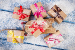 Wooden sled and wrapped gifts for Christmas or other celebration on snowy boards Royalty Free Stock Image