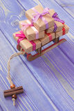 Wooden sled and wrapped gifts with ribbons for Christmas or other celebration Stock Image