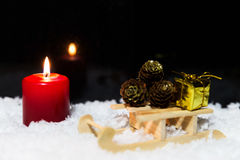 Wooden sledge with presents and candle in the snow, black backgr Royalty Free Stock Image