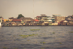 Wooden slums on stilts on the riverside of Chao Praya River in Bangkok, Thailand Royalty Free Stock Photography