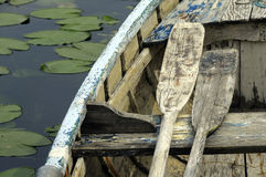 Wooden small boat and paddles stock photography