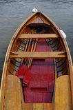 Wooden small boat and red paddles royalty free stock photo