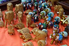 Wooden small figurines of various animals on the counter of a street shop stock image