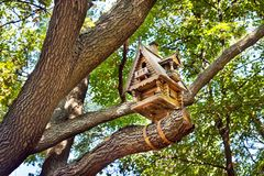 Wooden small hut birdhouse on a tree among the leaves. Carved wo royalty free stock image
