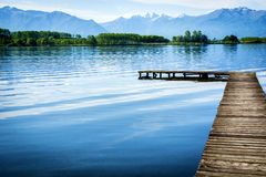 Wooden small pier over peaceful lake. Daytime shot Royalty Free Stock Photography