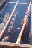 Wooden smoker. Ancient wooden smoker and racks with hot smoked sausages and meat royalty free stock photo