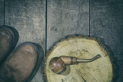 Wooden smoking pipe tobacco with a pair of leather boots Stock Photo
