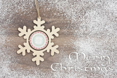 Wooden snowflake. On snow covered wood Stock Photos
