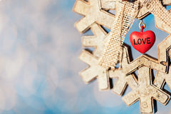 Wooden snowflake Christmas decoration with small red heart on sp Royalty Free Stock Image