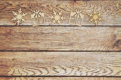 Wooden snowflakes and Christmas presents on a weathered wood bac stock images