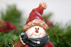 Wooden snowman with red cap. A wooden snowman with a red cap  and carrott nose in front of Christmas greenery Royalty Free Stock Photos