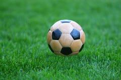 Wooden soccer. Ball in grass Stock Photos