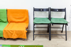 Wooden sofa with blankets and two black chairs in domestic room Stock Image
