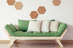 Wooden sofa with grey pillows. Grey pillows on green wooden sofa against white wall with natural cork Royalty Free Stock Photography
