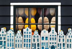 Dutch clogs behind a window and souvenir Amsterdam houses Stock Photo