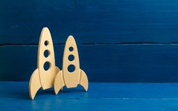 Wooden space rocket on a blue background. The concept of minimalism, high technologies and aspirations to conquer outer space. Bus royalty free stock photo