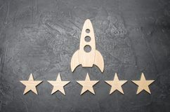 A wooden space rocket and five stars on a concrete background. The concept of space travel, commercial launches into space. Tourist flights to the orbit of the stock photography