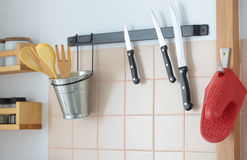 Wooden spatulas and knives on a rack Stock Photography