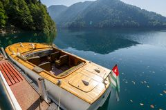 Wooden speed rarity boat at the pier on Lake Ritsa at the state residence. ABKHAZIA, GEORGIA, 17 SEPTEMBER 2017: Wooden speed rarity boat at the pier on Lake Royalty Free Stock Photography