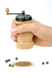 Wooden spice handmill in hand Stock Photos