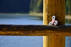 A wooden spinner lies on a wooden bar against a background of river water stock images
