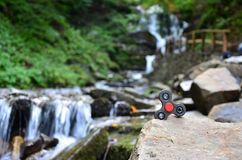 The wooden spinner lies on the rocks against the background of a small waterfall and a river.  stock photos