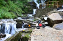The wooden spinner lies on the rocks against the background of a small waterfall and a river.  royalty free stock photos