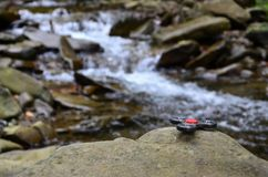 The wooden spinner lies on the rocks against the background of a small waterfall and a river.  stock photo