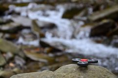 The wooden spinner lies on the rocks against the background of a small waterfall and a river.  royalty free stock photo