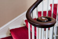 Wooden spiral handrail. Beautiful spiraling wooden handrail or bannister on a home staircase royalty free stock images