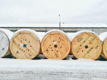 Wooden spool of power cables under the snow Royalty Free Stock Photos