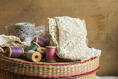 Wooden spools of multi color threads, rolls of beige and grey cotton lace on sewing rattan wicker basket, hobby, crafts Stock Image