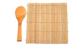 Wooden spoon beside bamboo placemat Stock Image