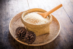 Wooden spoon in basket of jasmine rice and pine cones on wooden Stock Images