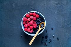Wooden spoon with bilberry and raspberries in blue bowl, the concept of organic berries on dark background. Berry picking. Copy space, close up, banner Stock Image