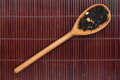 Wooden spoon with black tea Stock Image
