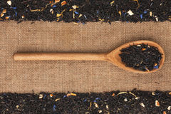 Wooden spoon with  black  tea  lies on  sackcloth Royalty Free Stock Images