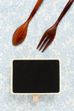 Wooden spoon and blank blackboard on blue table cl Stock Photo