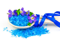 Wooden spoon with blue bath salt. Macro view of wooden spoon with blue bath salt and spring flowers isolated on white background Stock Photos