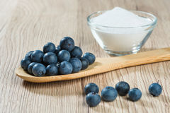 Wooden spoon with blueberries and glass bowl with sugar Royalty Free Stock Photos
