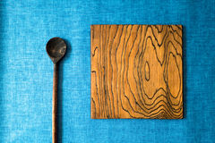 Wooden spoon and board on a blue fabric background Royalty Free Stock Image