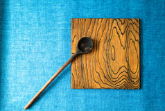 Wooden spoon and board on a blue fabric background Stock Images