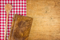 Wooden spoon and book on a wooden board Royalty Free Stock Images