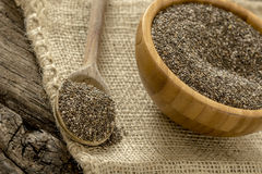 Wooden spoon and bowl full of healthy nutritious chia seeds. Lying on a burlap sac Royalty Free Stock Images