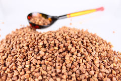 Wooden spoon with buckwheat groats Stock Photos