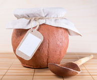 Wooden spoon and clay pot with cloth and empty label. On wooden background stock photography