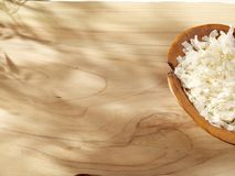 A wooden spoon with coconut chips on a sunny wooden background Royalty Free Stock Images