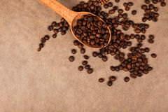 Wooden spoon with coffee beans. Lying on brown parchment Stock Photo