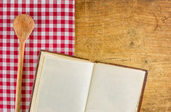 Wooden spoon and cookbook on a wooden board Stock Photography